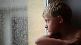 El niño pequeño solo mira las gotas de agua a través del vidrio de la ventana metrajes