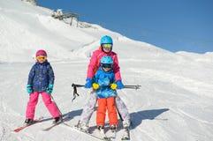 El niño pequeño sonriente con la familia aprende el esquí Foto de archivo libre de regalías