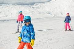 El niño pequeño sonriente con la familia aprendió el esquí durante vacat del invierno Imagen de archivo
