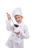El niño pequeño sonriente hermoso en sombrero del ` s del cocinero con la cucharón prueba el caldo cocinado fotos de archivo libres de regalías