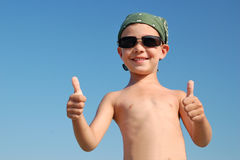 El niño pequeño sonriente muestra OK en el fondo del cielo Foto de archivo