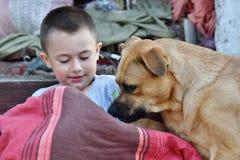 El niño pequeño sonriente se está divirtiendo con el perro agradable como los mejores amigos Foto de archivo libre de regalías