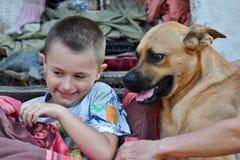 El niño pequeño sonriente se está divirtiendo con el perro agradable como los mejores amigos Imagen de archivo
