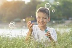 El niño pequeño sopla burbujas de jabón Fotografía de archivo