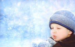 El niño pequeño sopla nieve con las manoplas Foto de archivo