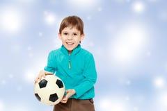El niño pequeño sostiene el balón de fútbol Imagenes de archivo