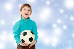 El niño pequeño sostiene el balón de fútbol Fotografía de archivo