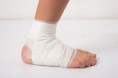 El niño pequeño tiene un accidente con su vendaje de la necesidad de la pierna Foto de archivo