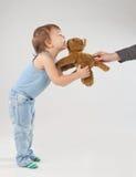 El niño pequeño toma un juguete, aislado en fondo ligero Imagen de archivo libre de regalías