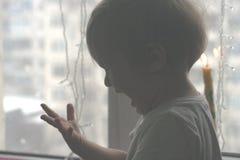 El niño pequeño travieso tocó el fuego de la vela imagenes de archivo