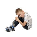 El niño pequeño triste se sienta en el piso que abraza sus rodillas Imagen de archivo