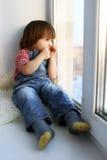 El niño pequeño triste se sienta en travesaño y mira fuera de ventana en wintertim Fotografía de archivo libre de regalías