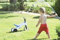 El niño pequeño vierte de una manguera en el jardín en un día de verano caliente en un césped verde, salpicando el agua Foto de archivo