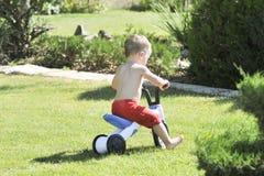 El niño pequeño vierte de una manguera en el jardín en un día de verano caliente en un césped verde, salpicando el agua Imagen de archivo libre de regalías