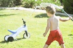 El niño pequeño vierte de una manguera en el jardín en un día de verano caliente en un césped verde, salpicando el agua Imagen de archivo