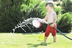 El niño pequeño vierte de una manguera en el jardín en un día de verano caliente en un césped verde, salpicando el agua Fotografía de archivo