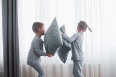 El niño pequeño y la muchacha efectuaron una lucha de almohada en la cama en el dormitorio Golpe travieso de los niños almohadas  fotos de archivo libres de regalías