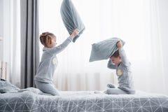 El niño pequeño y la muchacha efectuaron una lucha de almohada en la cama en el dormitorio Golpe travieso de los niños almohadas  imagenes de archivo