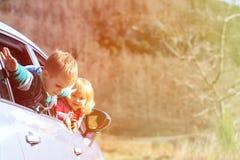 El niño pequeño y la muchacha felices viajan en coche en naturaleza Imagen de archivo