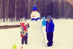 El niño pequeño y la muchacha juegan con el muñeco de nieve en naturaleza del invierno Fotos de archivo libres de regalías