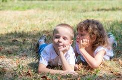 El niño pequeño y la muchacha mienten juntos en una hierba Imagenes de archivo