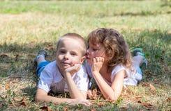 El niño pequeño y la muchacha mienten juntos en una hierba Imágenes de archivo libres de regalías