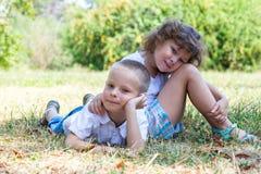 El niño pequeño y la muchacha mienten juntos en una hierba Imagen de archivo
