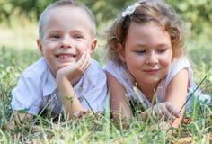 El niño pequeño y la muchacha mienten juntos en una hierba Foto de archivo libre de regalías
