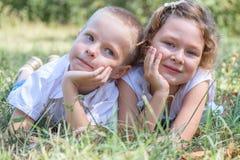 El niño pequeño y la muchacha mienten juntos en una hierba Fotos de archivo libres de regalías