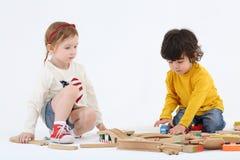 El niño pequeño y la muchacha se sientan en piso y construyen el ferrocarril Imagenes de archivo