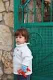 El niño pequeño y la puerta verde Foto de archivo