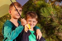 El niño pequeño y su hermano mayor están debajo de un paraguas multicolor brillante foto de archivo libre de regalías