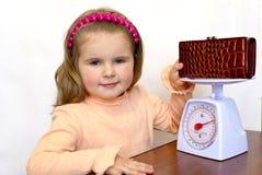 El niño pesa un monedero con el dinero Foto de archivo
