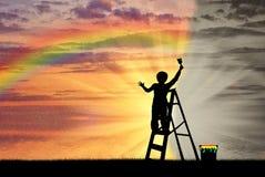 El niño pinta el paisaje marino con un arco iris Imagen de archivo libre de regalías