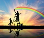 El niño pinta el paisaje marino con un arco iris Imagenes de archivo