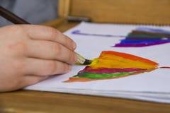 El niño pinta en la acuarela, pintura Dibujo del ` s de los niños El niño dibuja un paraguas en todos los colores del arco iris imagen de archivo libre de regalías