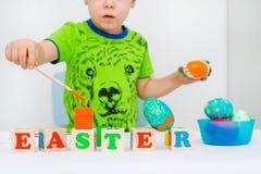 El niño pinta los huevos de Pascua fotografía de archivo libre de regalías