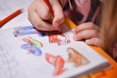 El niño pinta sobre las imágenes de los lápices que colorean los zapatos imagenes de archivo