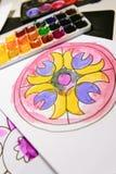 El niño pinta un libro de colorear para los adultos con la acuarela Foto de archivo