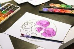 El niño pinta un libro de colorear para los adultos con la acuarela Imagen de archivo