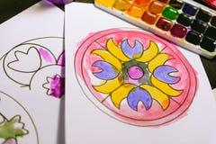 El niño pinta un libro de colorear para los adultos con la acuarela Imágenes de archivo libres de regalías