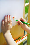 El niño pinta una flor en una hoja del papel Foto de archivo libre de regalías