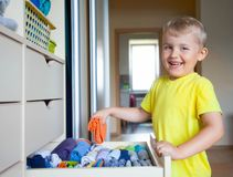 El niño pone su ropa El muchacho saca de la camiseta Fotografía de archivo libre de regalías