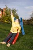 El niño positivo se sienta en diapositiva con aro de la hierba verde Foto de archivo libre de regalías