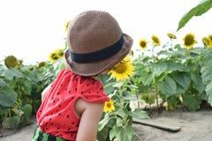 El niño precioso está alrededor de vacaciones de verano de la flor del sol Foto de archivo