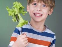 El niño precioso le gusta la ensalada Foto de archivo libre de regalías