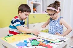 El niño preescolar crea una imagen con formas Fotos de archivo