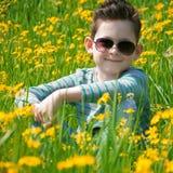 El niño preescolar precioso tiene un resto en un prado de la flor Él se sienta Foto de archivo libre de regalías