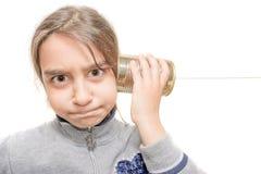 El niño preocupante oye del teléfono construido con la lata Imagen de archivo