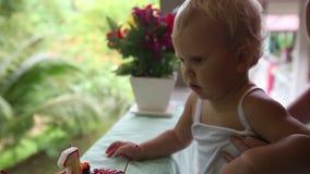 El niño primero vio la torta para mi cumpleaños por un año con las cerezas con la vela almacen de metraje de vídeo